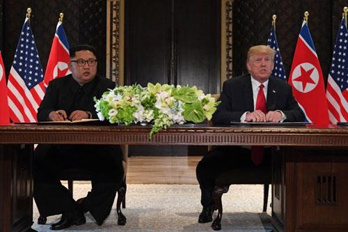 Lãnh đạo Triều Tiên Kim Jong-un và Tổng thống Mỹ Donald Trump ký tuyên bố chung tại Singapore. Ảnh: StraitsTimes.