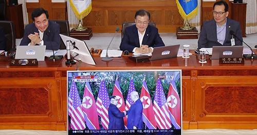 Tổng thống Moon Jae-in (giữa) theo dõi thời khắc lịch sử qua TV trong phòng họp nội các. Ảnh: Yonhap