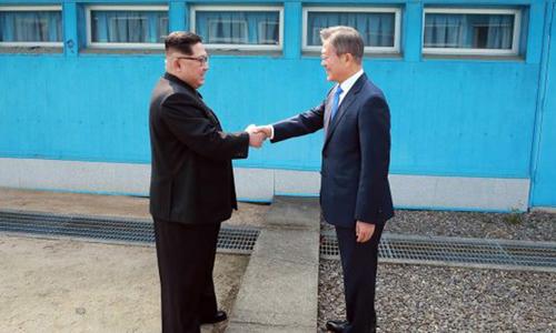 Tổng thống Hàn Quốc Moon Jae-in bắt tay lãnh đạo Triều Tiên Kim Jong-un tại ranh giới quân sự phân chia hai miền hôm 27/4. Ảnh: AFP.