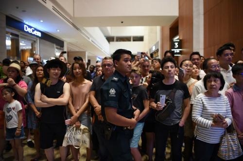Cảnh sát Singapore đứng trước đám đông người muốn quan sát Kim Jong-un tại khách sạn Marina Bay Sands ở Singapore ngày 11/6. Ảnh: AFP.