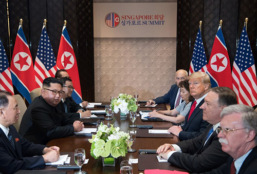 Interpreter Lee Yun-hyang (second to right) sits next to US President Donald Trump as he shakes North Korean leader Kim Jong-uns hand over a table during their meeting at Capella Hotel in Singapore, Tuesday. (AP-Yonhap)