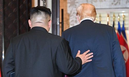 Kim Jong-un (trái) và Donald Trump cùng rời phòng hội nghị sau lễ ký kết thỏa thuận ngày 12/6 ở khách sạn Capella, trên đảo Sentosa, Singapore. Ảnh: AFP.