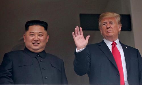 Tổng thống Mỹ Donald Trump vẫy tay cạnh lãnh đạo Triều Tiên Kim Jong-un ở khách sạn Capella, Singapore hôm 12/6. Ảnh: Reuters.