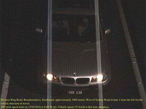 Ảnh kèm phiếu phạt cho thấy một chiếc BMW cùng biển số, tuy khác màu của biển, đang chạy quá tốc độ. Ảnh: 9 News.