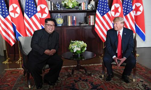 Lãnh đạo Triều Tiên Kim Jong-un (trái) và Tổng thống Mỹ Trump hội đàm trong thư viện của khách sạn Capella. Ảnh: AFP.