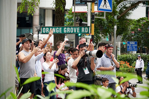 Photographers and members of the public getting ready to snap pictures of Mr Kims motorcade at the junction of Orange Grove and Orchard roads. Over the past days, crowds have gathered around the St Regis and Shangri-La, where the leaders stayed. PHOTO: LIN ZHAOWEI FOR THE STRAITS TIMES