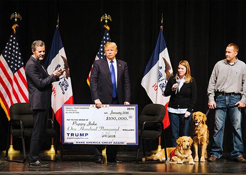 Donald Trump (giữa) trao một tấm séc trị giá 100.000 USD cho tổ chức giải cứu vật nuôi Puppy Jake hồi tháng 1/2016 ở thành phố Davenport, bang Iowa. Ảnh: Time.