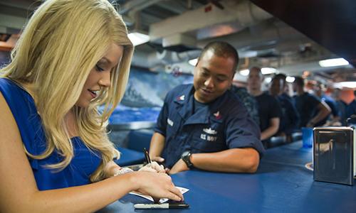 Cựu hoa hậuTeresa Scanlon ký tên tặng các thủy thủ đóng quân trên tàuUSS Cape St. George năm2012. Ảnh: DVIDS.