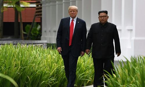 Tổng thống Mỹ Donald Trump (trái) và lãnh đạo Triều Tiên đi dạo trong khuôn viên khách sạn Capella, trên đảo Sentosa, Singapore ngày 12/6/. Ảnh: Reuters.