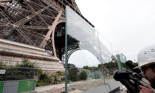 Hàng rào bằng kính dày 6,5 cm tạo thành hai mặt bảo vệ tháp Eiffel. Ảnh: Reuters.