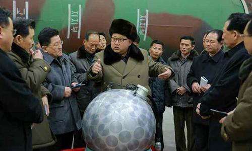 Lãnh đạo Triều Tiên Kim Jong-un đứng cạnh thiết bị được cho là đầu đạn hạt nhân trong chuyến thị sát cơ sở sản xuất tên lửa tháng 3/2016. Ảnh: Korea Times.