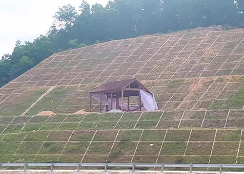 Căn nhà gỗ được ông Thắng cùng người thân dựng trên mái đập dâng 10 hôm trước. Ảnh: Đ.H