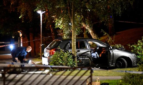 Cảnh sát khám xét một chiếc xe liên quan tới vụ xả súng ở thành phố Malmo, Thụy Điển tối ngày 18/6. Ảnh: TT News Agency/Reuters.