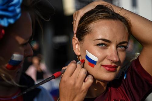 Một nữ cổ động viên Nga vẽ cờ lên mặt để cổ vũ đội nhà trong trận gặp Ai Cập hôm 19/6. Ảnh: AFP
