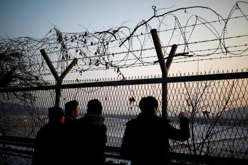 Những du khách đứng bên phía Hàn Quốc nhìn sang phía Triều Tiên qua hàng rào dây thép gai phân chia hai miền. Ảnh: Reuters.