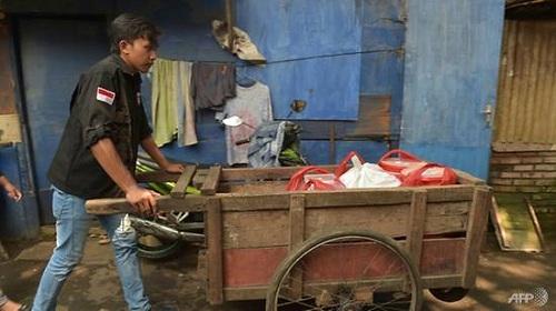 Một tình nguyện viên đi phát thức ăn thừa cho người nghèo ở khu ổ chuột Jakarta. Ảnh: AFP.