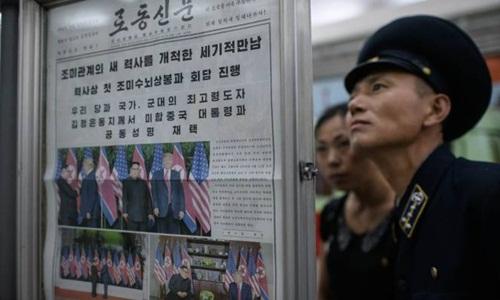 Người dân Triều Tiên đọc thông tin về hội nghị thượng đỉnh Trump - Kim trên tờ Rodong Sinmun. Ảnh: AFP.