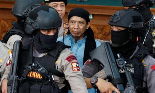 Nhân viên chống khủng bố áp giải Aman Abdurrahman (áo xanh) rời tòa án hôm nay. Ảnh: Reuters.