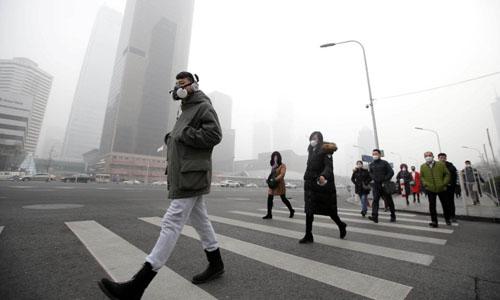 Người dân Trung Quốc bịt khẩu trang kín mít khi ra đường vì ô nhiễm môi trường. Ảnh: Reuters.
