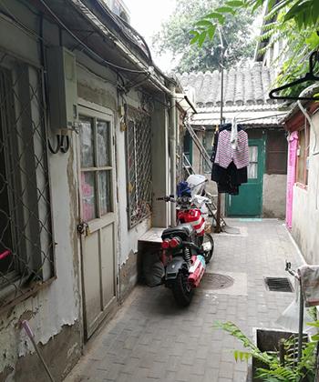 Hẻm dẫn vào căn hộ cửa gỗ màu xanh. Ảnh: SCMP.