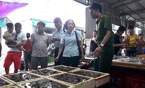 Thanh tra liên nghành lập biên bản niêm phong số hàng tôm sống nghi bị bơm hoá chất. Ảnh: Lam Sơn.
