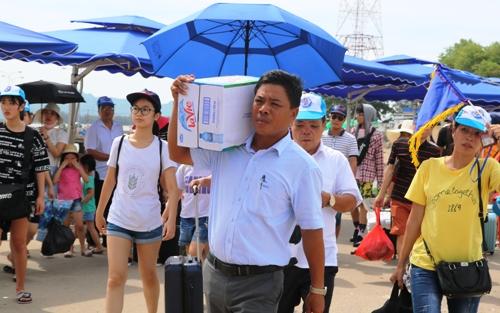 Ông Nguyễn Văn Vang, Bến trưởng Bến phà Gót- Cái Viềng (Hải Phòng) làm cửu vạn cùng nhiều nhân viên chuyển hàng lý cho khách xuống phà trong ngày đầu thực hiện lệnh cấm xe khách từ 29 chỗ trở lên. Ảnh: Giang Chinh