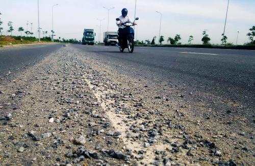 Mặt đường 356 đoạn từ địa bàn phường Đông Hải 2, quận Hải An qua cầu vượt biển sang huyện đảo Cát Hải cát, đá rơi vãi đầy đường, tiềm ẩn nguy cơ mất an toàn giao thông cho các phương tiện.