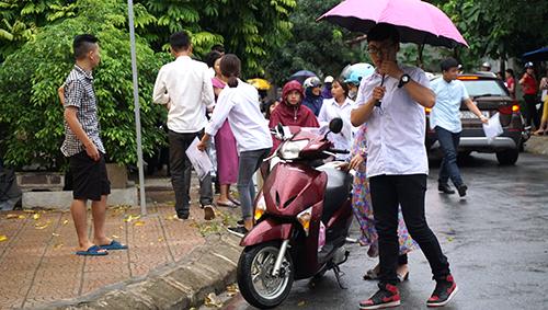Cơn mưa rào bất chợt khiến phụ huynh, học sinh đến trường thi vất vả hơn do phải mang theo áo mưa hoặc ô. Ảnh: Lê Hoàng.