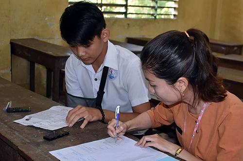 Cán bộ điểm thi được phân công viết bài thi cho thí sinh Phạm Quốc Sơn. Ảnh: An Phú