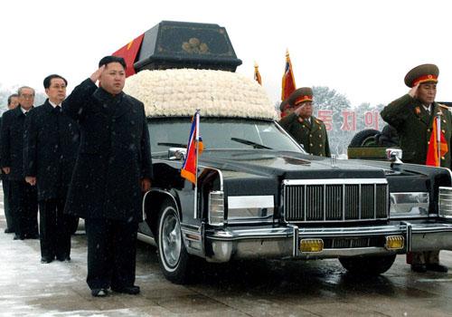 Lãnh đạo Triều Tiên Kim Jong-un (trái) đứng bên cạnh chiếc xe Lincoln Continental chở linh cữu cố lãnh tụ Kim Jong-Il. Ảnh: AP.