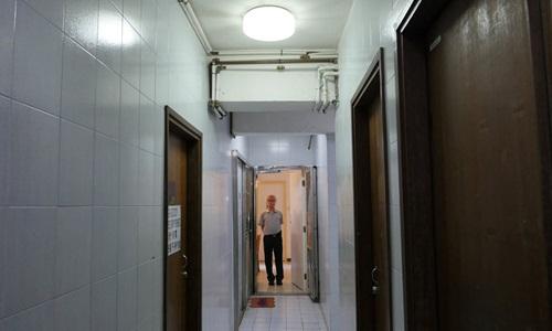 Ng Goon-lau đứng nhìn ra từ bên trong căn hộ ma ám ông sở hữu. Ảnh: Reuters.