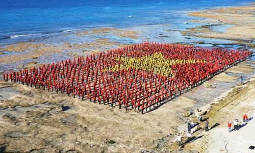 Cờ tổ quốc do 3.000 người tạo hình bên bờ biển Hang Cau, Lý Sơn. Ảnh: Thạch Thảo.