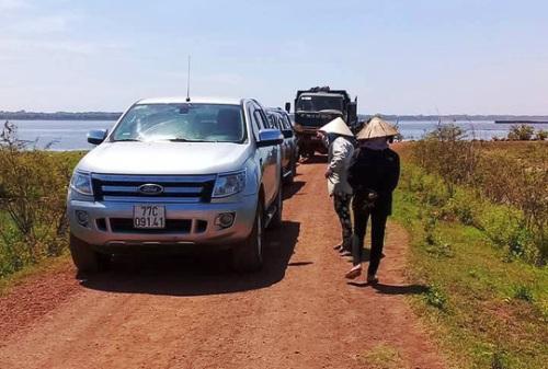 Các ôtô của đoàn khảo sát bị người dân giữ gần đầm Trà Ổ. Ảnh: Nam Anh.