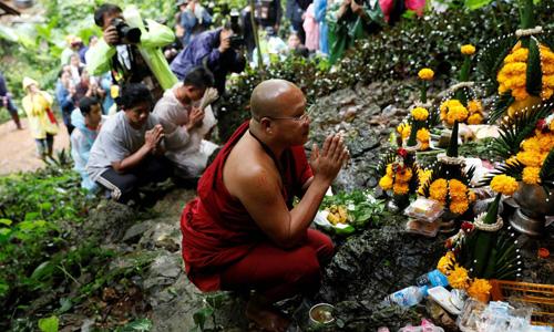Một nhà sư và thân nhân các cậu bé mắc kẹt cầu nguyện gần khu vực hang Tham Luang. Ảnh: Reuters.