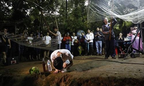 Người thân của các em nhỏ trong đội bóng bị mắc kẹt hôm 26/6 cầu nguyện bên ngoài hang Tham Luang. Ảnh: AFP.