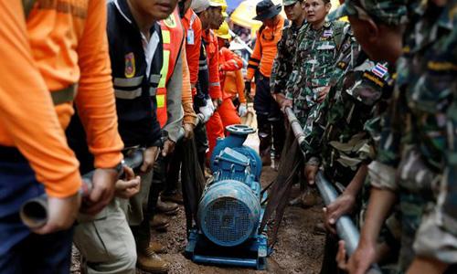 Đội cứu hộ chuyển một máy bơm tới khu vực hang Tham Luang, nơi đội bóng nhí Thái Lan mắc kẹt. Ảnh: Reuters.