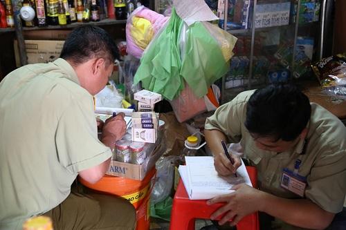 Lực lượng chức năng làm biên bản xử lí cửa hàng buôn bán thuốc lá nhập lậu.