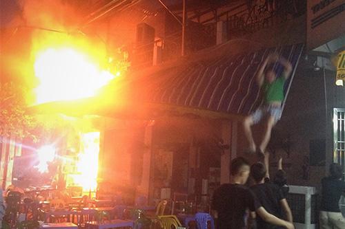 Một người nhảy từ tầng hai quán bia xuống đất. Ảnh: Gia Chính.