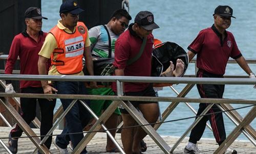 Thi thể một nạn nhân thiệt mạng trong vụ chìm tàu Phoenix được đưa lên bờ. Ảnh: AFP.