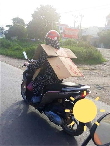 Một Ninja, theo cách gọi của cư dân mạng dành cho phụ nữ, sử dụng bìa carton để che chắn trước sau dù đã mang đầy đủ đồ chống nắng.