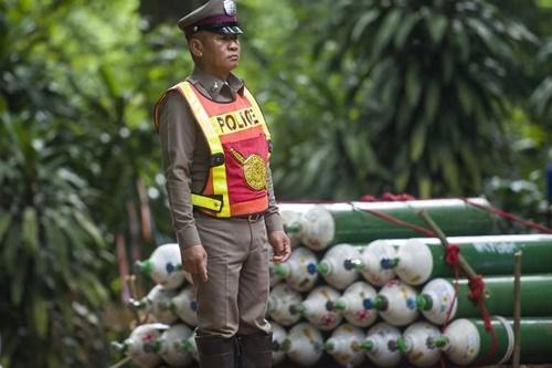Một cảnh sát Thái Lan đứng canh giữ các bình oxy sử dụng trong chiến dịch giải cứu đội bóng nhí. Ảnh: AFP.