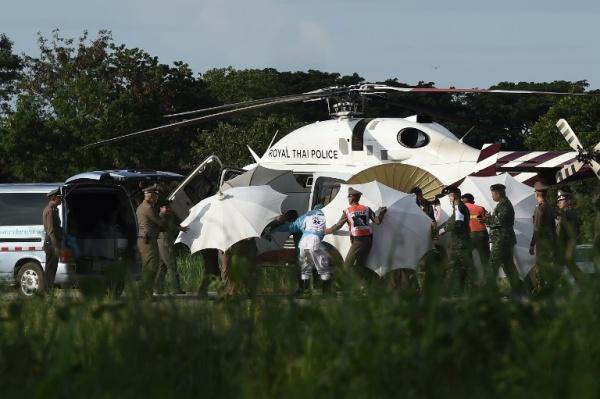 Giới chức dùng ô che cáng được vận chuyển từ trực thăng tới xe cứu thương. Ảnh: Reuters.