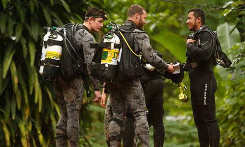 Cảnh sát Liên bang và Lực lượng Quốc phòng Australia trò chuyện cùng một nhân viên cứu hộ Thái Lan hôm 3/7. Ảnh: AP.