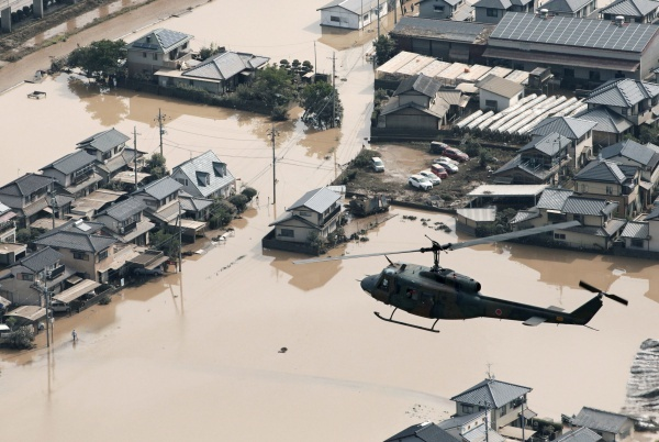 A helicopter flies over Mabi town which was flooded by the heavy rain in Kurashiki, Okayama Prefecture, Japan, in this photo taken by Kyodo July 9, 2018. M