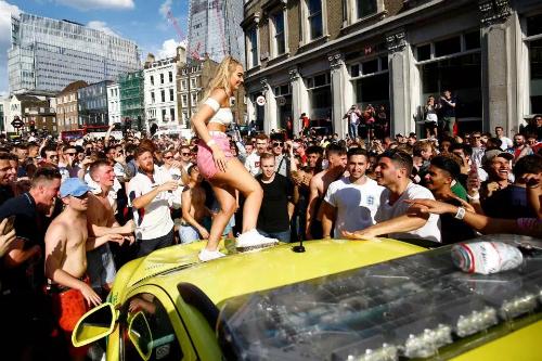 Một cô gái trèo lên nóc ca-pô xe cấp cứu nhảy múa trước sự cổ vũ của đám đông. Ảnh: Reuters.