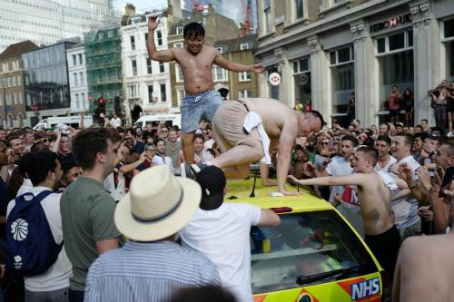 Hai người đàn ông cởi trần trèo hẳn lên nóc xe thực hiện những vũ điệu cuồng nhiệt mừng đội Anh giành chiến thắng. Ảnh: AFP.