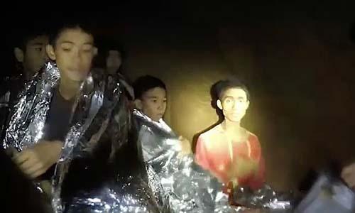 Adul Sam-on (áo đỏ, bên phải) là cậu bé đã giao tiếp với các thợ lặn bằng tiếng Anh. Ảnh: Hải quân Thái Lan.