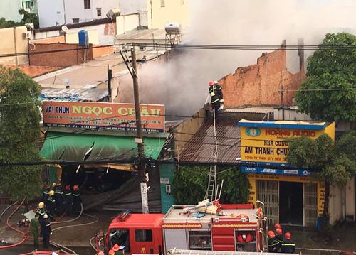 Cảnh sát leo mái nhà dập lửa. Ảnh: Tin Tin