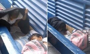 Cô bé vô gia cư đội mưa làm bài tập về nhà