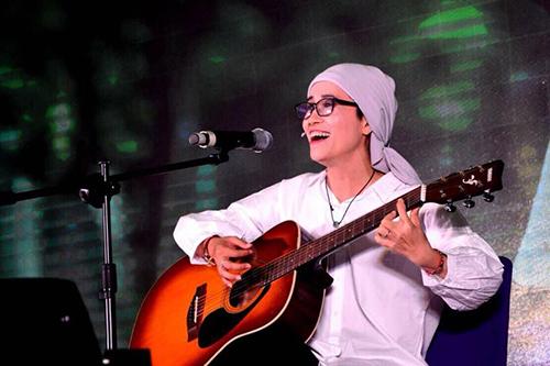 Chị Nguyễn Thuý Hương ôm đàn guitar hát bài Ngẫu hứng Đông Hà trong đêm nhạc từ thiện. Ảnh: NVCC